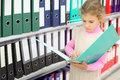 Serious looks at folder and stands near to shelves Stock Photography