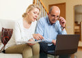 Serious man adn woman reading finance documents together men women and using laptop in home interior Royalty Free Stock Photography