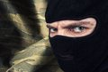Serious man in a balaclava mask against military camouflage background Stock Photo