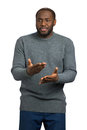 Serious man in grey sweater gesticulating. Royalty Free Stock Photo