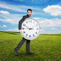 Serious man holding big clock Royalty Free Stock Photo