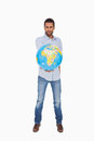 Serious man holding out a globe on white background Stock Image
