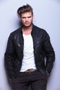 Serious man in leather jacket standing against gray wall young looks at the camera Stock Photos