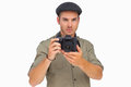 Serious man in peaked cap taking photo on white background Royalty Free Stock Image
