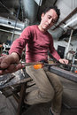 Serious man shaping hot glass object with big tools Royalty Free Stock Photo