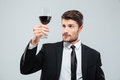 Serious man sommelier in suite tasting red wine in glass Royalty Free Stock Photo