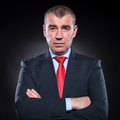 Serious mature business man with hands folded looking at the camera on black background Stock Images