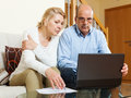 Serious mature couple looking documents in laptop home interior Royalty Free Stock Photo