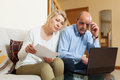 Serious mature man and woman reading finance documents men women in home interior Stock Photo