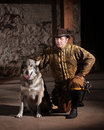 Serious mature medieval mercenary kneeling next to dog Royalty Free Stock Images