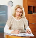 Serious mature woman reading documents at table Stock Photos