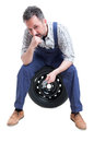 Serious mechanic man sitting on black tire Royalty Free Stock Photo