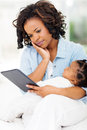 Serious mother tablet african holding baby while using computer Royalty Free Stock Photo