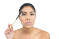 Serious nude brunette using eyebrow brush on white background Royalty Free Stock Photo