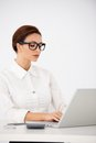 Serious office woman typing on laptop pretty young wearing white long sleeve shirt and eyeglasses computer at the table seriously Royalty Free Stock Image