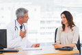 Serious patient talking with her doctor about illness in medical office Stock Photo