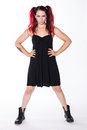 Serious punk girl in combat boots and black dress a with red dyed hair poses with a look against a white background Royalty Free Stock Images