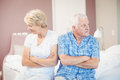 Serious senior couple sitting on bed at home looking away while Stock Photos