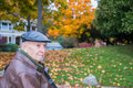 Serious senior man outside with autumn background sad looking or pensive elderly in urban residential park fall colors in Stock Photo
