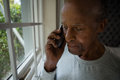 Serious senior man talking on mobile phone by window Royalty Free Stock Photo