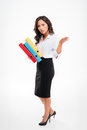 Serious smart asian businesswoman holding binders waving hand Royalty Free Stock Photo