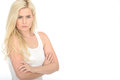 Serious stern moody young woman standing with her arms folded in late twenties looking at the camera wearing a white vest top Royalty Free Stock Photos