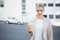 Serious stylish businesswoman holding coffee outside on urban background Royalty Free Stock Image