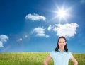 Serious stylish businesswoman posing hands on hips composite image of meadow under sunny sky Stock Photos