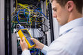 Serious technician using digital cable analyzer on server Royalty Free Stock Photo