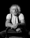 Serious tough old man with wild hair in monochrome isolated on black Stock Image
