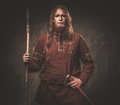 Serious viking with a spear in a traditional warrior clothes, posing on a dark background. Royalty Free Stock Photo