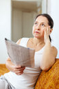 Serious and wistful woman with newspaper at home Stock Photos