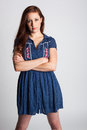 Serious woman in calico dress a young wearing a blue looks intently with folded arms Royalty Free Stock Image