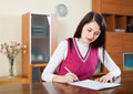 Serious woman filling in financial documents at table home interior Royalty Free Stock Image