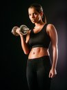 Serious woman lifting a dumbbell photo of toned young female exercising with dumbbells Royalty Free Stock Photography