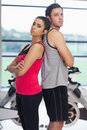 Serious woman and man standing back to back in gym side view portrait of a young women men a bright Royalty Free Stock Photos