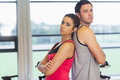 Serious woman and man standing back to back in gym side view portrait of a young women men a bright Royalty Free Stock Photography