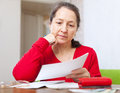 Serious woman reads payment bills mature at home Stock Photos