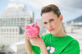 Serious woman wearing green recycling tshirt holding piggy bank outside on a sunny day Royalty Free Stock Images