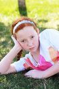 Serious young girl auburn hair relaxes outside grass Royalty Free Stock Image