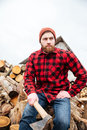 Serious young handsome man sitting on logs and holding axe Royalty Free Stock Photo