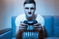 Serious young man playing a video game at home Royalty Free Stock Photo