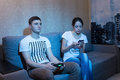 Serious young man playing a video game sitting with his girlfrie Royalty Free Stock Photo