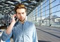 Serious young man talking on mobile phone inside building Royalty Free Stock Photo