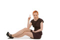 Serious young redhead woman pointing above her head her finger to blank copyspace as sits floor white background Royalty Free Stock Photography