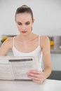 Serious young woman reading a newspaper in the kitchen at home Royalty Free Stock Image