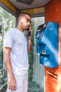 Seriously asian man using  payphone Royalty Free Stock Photo