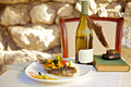 Served table in a restaurant on the stuffed fish with vegetables and bottle of white wine Royalty Free Stock Photos