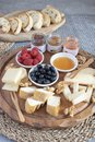 Served table - wine appetizer, cheese assortment on round wooden board, walnuts, berries, honey, jams, bread, copy space Royalty Free Stock Photo