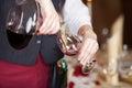 Serveerster pouring red wine in wijnglas van karaf Stock Afbeeldingen